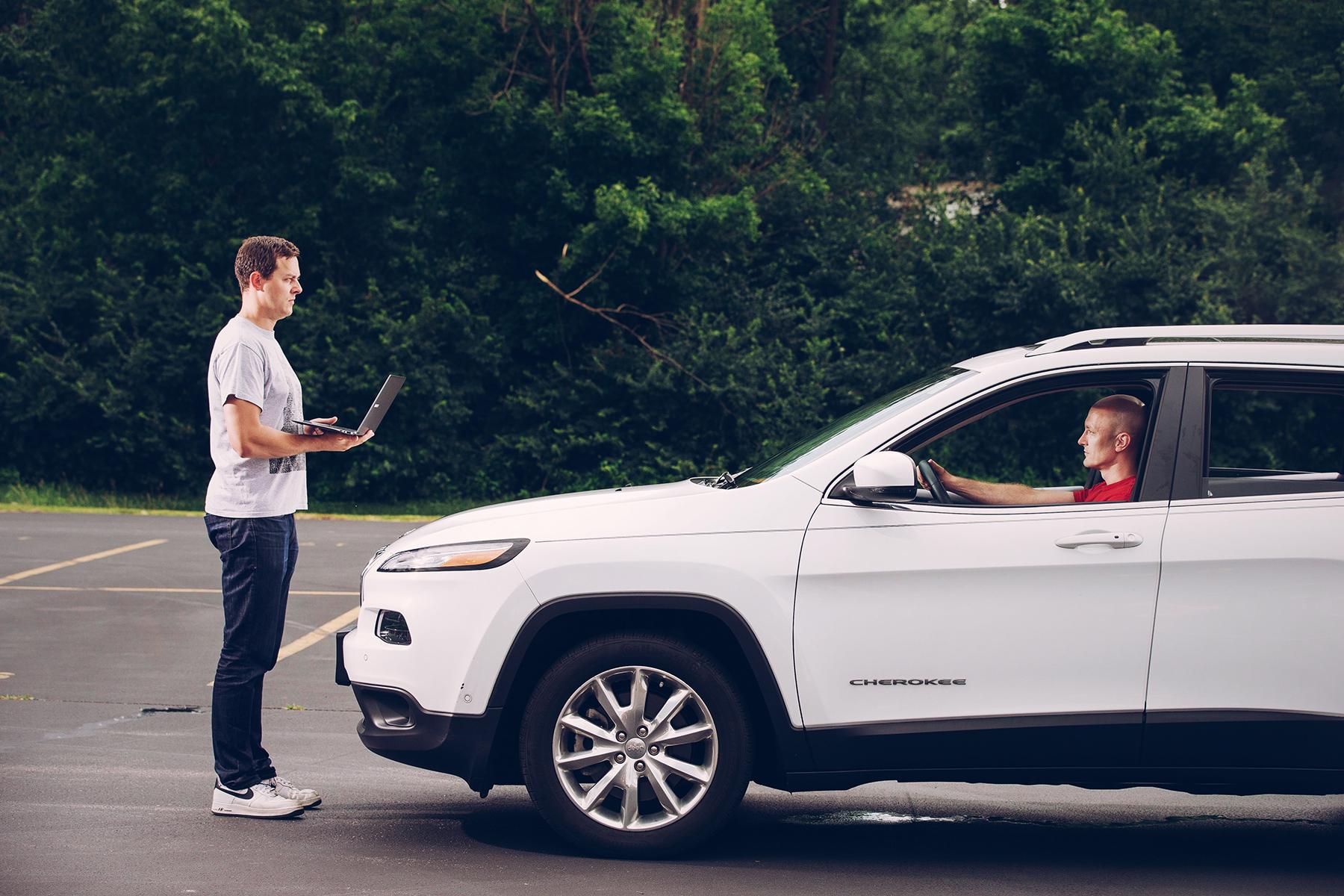 Charlie Miller e Chris Valasek esperti di vulnerabilità digitale delle auto mentre fermano una auto collegandosi da remoto al suo sistema elettronico.
